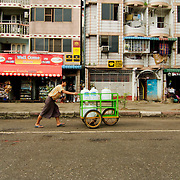 Mau pushing cart with water containers in the streets of Yangon
