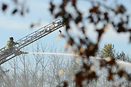 A firefighter continues to pour water on hot spots Friday November 17, 2017 after a 5-alarm fire at Barclay Friends Nursing Home in West Chester, Pennsylvania. The fire has displaced at least 200 residents of the facility. (WILLIAM THOMAS CAIN/ For The Philadelphia Inquirer)