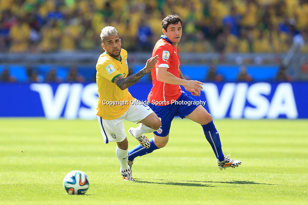 28th June 2014 - FIFA World Cup - Round of 16 - Brazil v Chile - Daniel Alves of Brazil battles with Eugenio Mena of Chile - Photo: Simon Stacpoole / Offside.