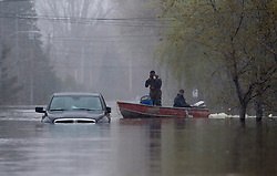 Two men pass a submerged truck as they leave a home in a flooded area of Gatineau, Quebec, Canada., Monday, May 8, 2017. Photo by Adrian Wyld /The Canadian Press/ABACAPRESS.COM