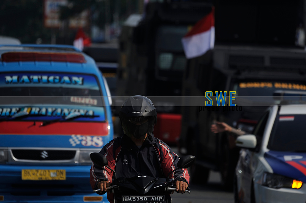 Medan, Indonesia, March 28, 2020: A motorist seen using mask crossing the Sisingamangaraja street beside the daily socialization and disinfection of the Corona Virus Disease 19 spread dangers in Medan, North Sumatra province, Indonesia on March 28, 2020.