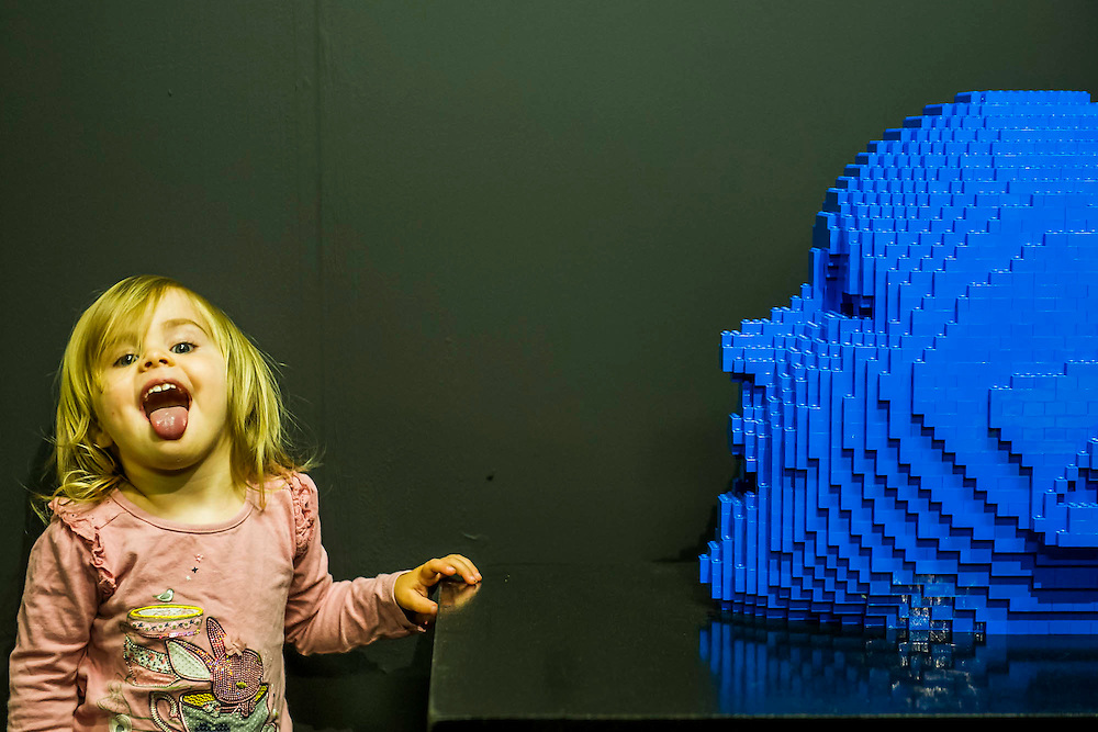 Evie, aged 2 and a bit, and her mum enjoy the show. The Art of the Brick (in LEGO) by Nathan Sawaya -  over a million pieces of Lego® make up over 80 sculptures, including: replicas of artworks such as The Mona Lisa and Michelangelo's David; personal works in dedicated to 'The Human Condition'; a 'British' room full of exhibits created for London;'Dinosaur', the biggest of all the sculptures created from over 80,000 bricks; and 'Yellow' which Lady Gaga recently commissioned for her G.U.Y. video.  The exhibition runs from 26 Sept 2014 to 04 Jan 2015. The Truman Brewery, Brick Lane, London, UK 24 Sept 2014