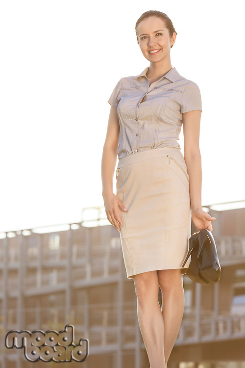 Happy young businesswoman holding footwear in front of office building