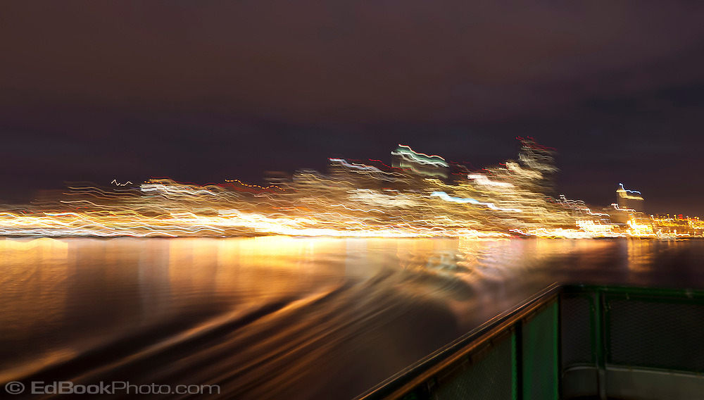 Leaving Hurry Hurry Land - a view of Seattle and ferry wake with motion blur streaking the cityscape.