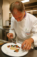 Chef Eric Frechon prepares the garnitures on the plate for the poulard de bresse.. Hotel Bristol, Paris.....photo by Owen Franken