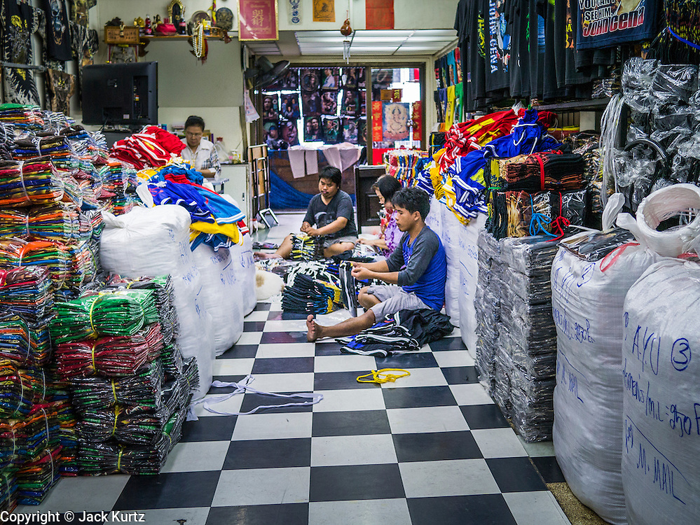 30 MAY 2013 - BANGKOK, THAILAND:   Workers bundle clothes for shipment in a market stall in Bobae Market in Bangkok. Bobae Market is a 30 year old famous for fashion wholesale and is now very popular with exporters from around the world. Bobae Tower is next to the market and  advertises itself as having 1,300 stalls under one roof and claims to be the largest garment wholesale center in Thailand.   PHOTO BY JACK KURTZ