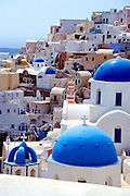Oia, Santorini Island, Greece: blue church domes and a maze of multilevel houses. Geologic and human history of Santorini: Humans first arrived around 3000 BC on this volcano known in ancient times as Thira (or Thera). The island was a volcanic cone with a circular shoreline until 1646 BC, when one of earths most violent explosions blasted ash all over the Mediterranean, sunk the center of the island, launched tidal waves, and may have ruined the Minoan civilization 70 miles away on Crete. Remarkably, volcanic ash dumped onto the volcanos flanks actually preserved the village of Akrotiri and its 3600-year-old frescoes from the Minoan era. These are some of the earliest known examples of world art history, which you can now view in museums. In 286 BC, the volcano split off Thirasia (Little Thira) Island (to the West). The volcano began rebuilding, and in 197 BC the small center islet of Palia Kameni appeared. In 1707 CE, lava started forming Nea Kameni, the larger center island which erupted as recently as 1956 and caused a huge earthquake (7.8 on the Richter scale) which destroyed most of the houses in the towns of Fira and Oia. Fira and Oia have since been rebuilt as multi-level mazes of fascinating whitewashed architecture, attracting tourists from around the world.