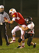 Marion's Trevor Hardman (7) is sacked by Solon's Jordan Wymer (24) during the first half of the game between the Solon Spartans and the Marion Indians at Thomas Park Field in Marion on Friday evening, October 5, 2012.