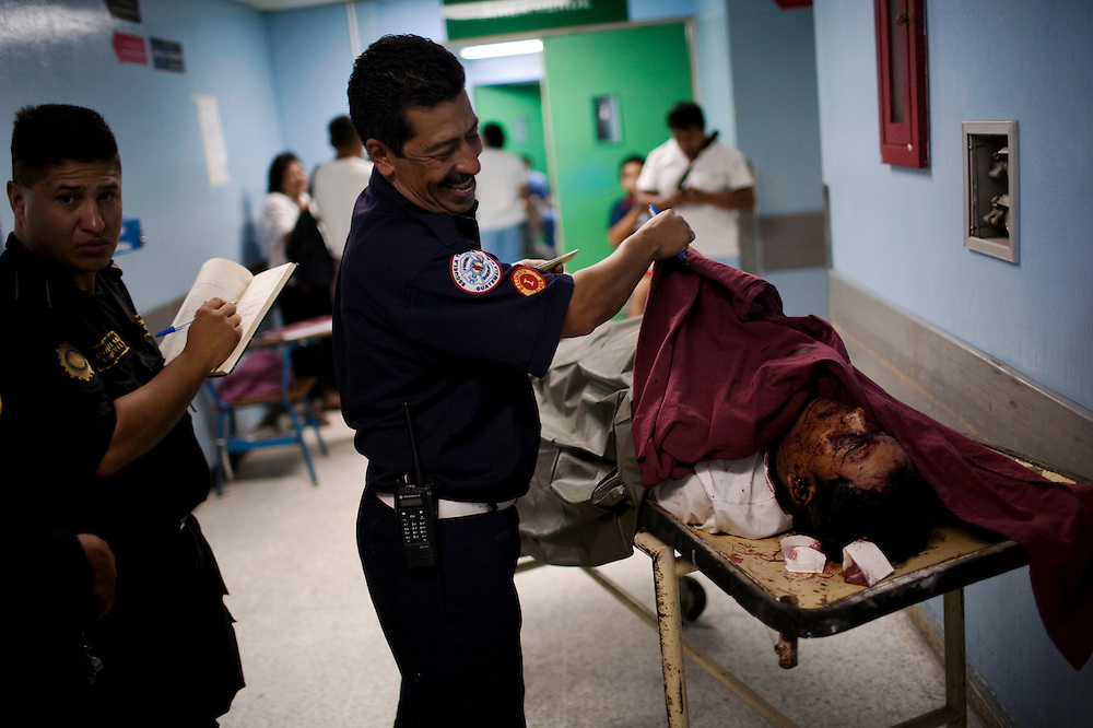 A firefighter laughs as looking to a man who died after entering the emergency room of  the San Juan de Dios hospital, Guatemala City, Thursday, July 1, 2010. (AP Photo/Rodrigo Abd)