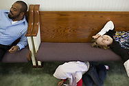 "Khalil looks at Rashid Weekley, his father Abdul-Hakim's best friend, while Weekley's daughter Layla plays on the floor inside Pittsburg Masjid on October 29, 2010. Rashid has since gone through a divorce, so Khalil and his best friend Kai Weekley rarely see each other in person. ""They'll text, they'll talk on the phone or they'll play games on the Playstation together where they can talk—(It) kind of hurts him that he kind of lost his best friend in a divorce,"" Abdul-Hakim said."