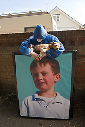 © Licensed to London News Pictures. 19/09/2011. Crays Hill, UK. An activist holding a dog standing over a picture of one of the Dale Farm travellers  today (19/09/2011).  Activists and residents at the Dale Farm travellers site in Essex prepare for the council to enforce an eviction notice which is due to start today (19/09/2011). Photo credit: Ben Cawthra/LNP