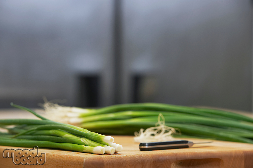 Fresh spring onions and knife on chopping board close-up
