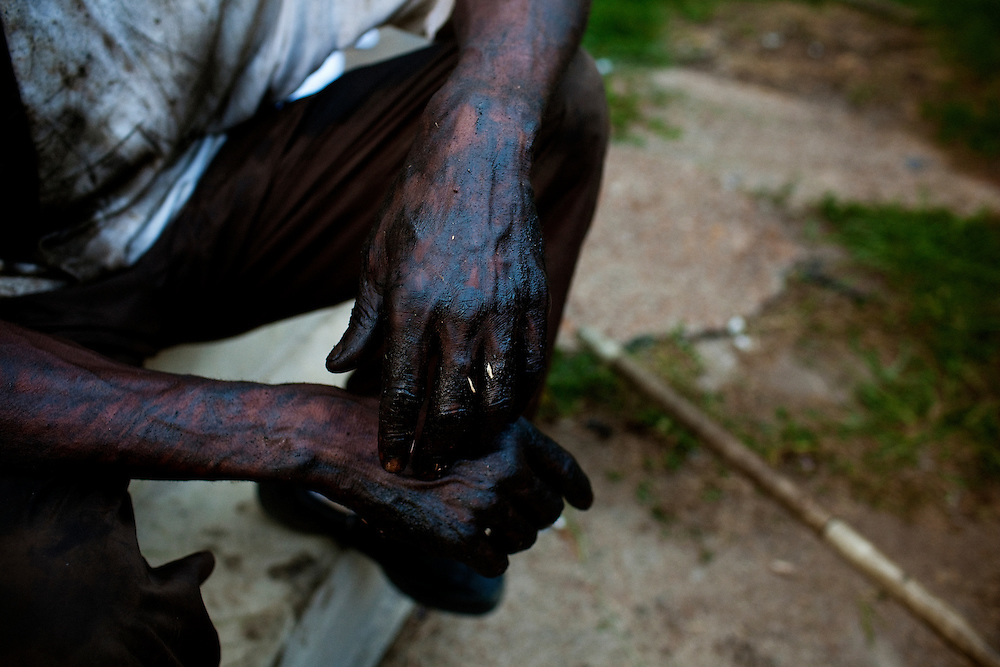 A man's hands are covered in car oil after working on a car in the Baptist Town neighborhood of Greenwood, Mississippi on July 3, 2010.
