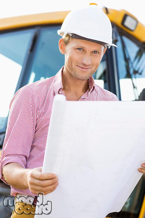 Portrait of male architect holding blueprint at construction site