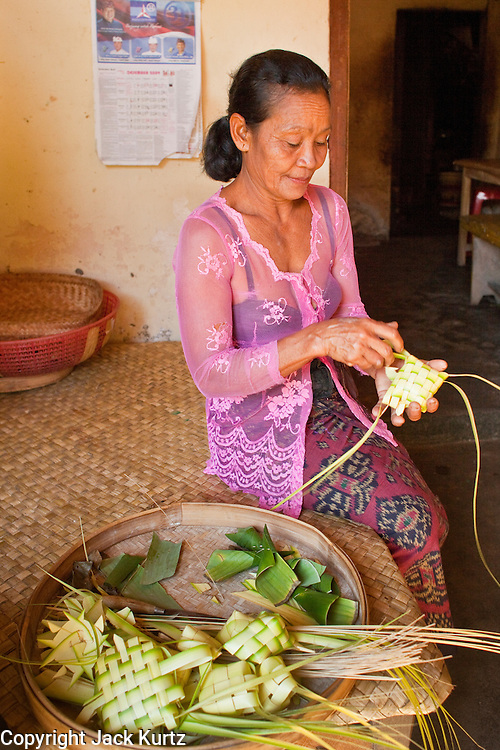 """Apr. 22 - UBUD, BALI, INDONESIA:  A woman in Ubud, Bali, Indonesia, makes baskets for temple offerings before a Odalan ceremony in her family temple. The Odalan ceremony is the """"birthday"""" ceremony for Hindu temples in Bali and are held every 210 days. They are common in Bali.    Photo by Jack Kurtz/ZUMA Press."""