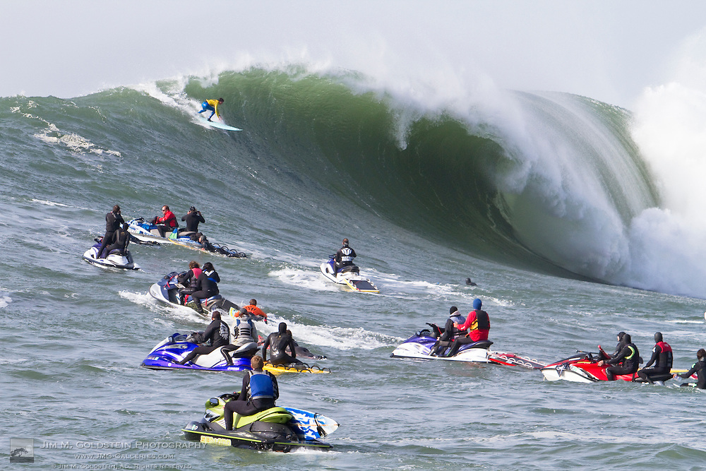 2nd place finisher Shane Desmond descends a giant wave in the final round of the 2010 Mavericks Surf Contest