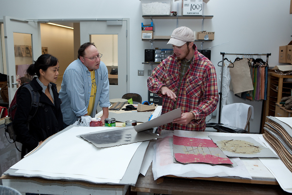 Melissa, (left) Mattew Reedy center) and Drew Cameraon  (right) looking at samples from the workshop. Combat Paper participants in a workshop in the Paper Lab in the Department of Art at the University of Wisconsin-Madison.