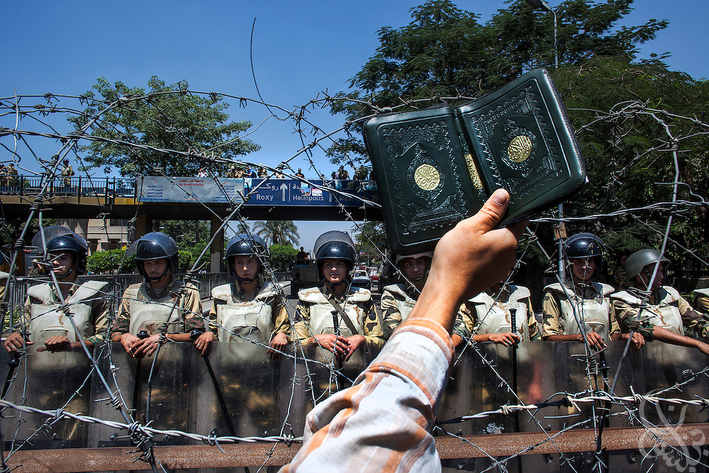 A Koran is held aloft as a group of female Muslim Brotherhood members and other supporters of deposed Egyptian president Mohamed Morsi gather in protest at the barbed wire barricades leading to near the Defense Ministry building in the Abbasiya district of Cairo Friday July 30, 2013.  The Muslim Brotherhood has maintained a steady wave of protests and sit-ins for a month since Morsi was deposed by the Egyptian military and replaced by an interim government, and vow to continue until he is reinstated.