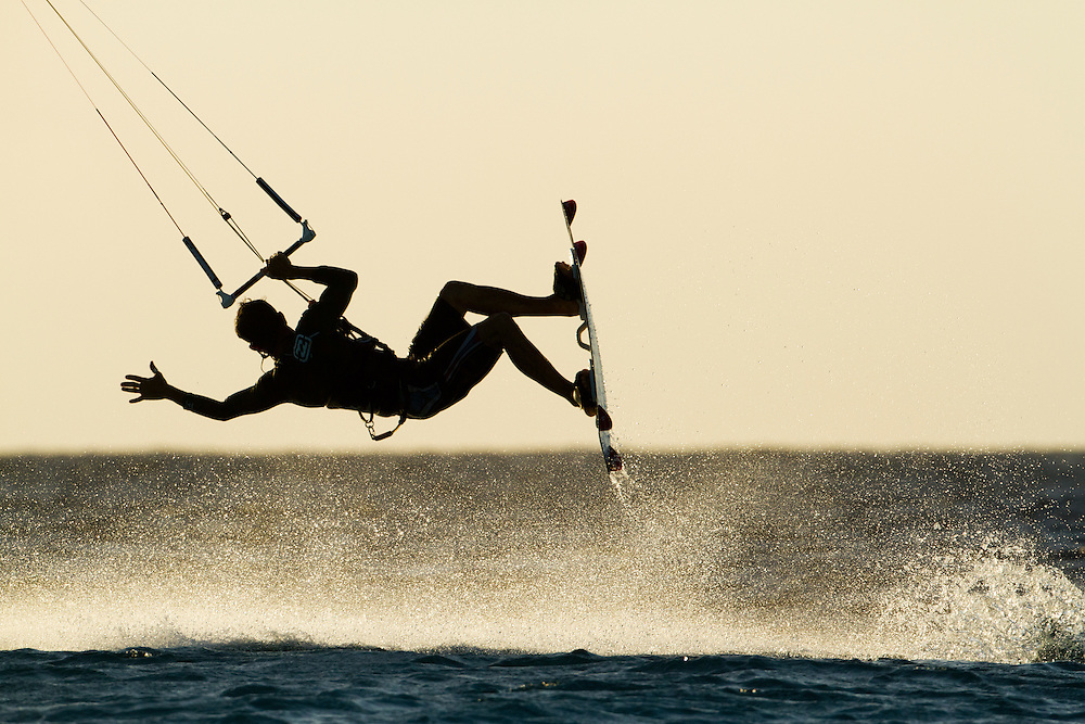 Dutch Antilles, Bonaire, Silhouette of Kitesurfer catching air above breaking waves at sunset on Caribbean Sea