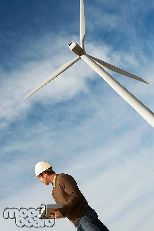 Engineer wearing hardhat near wind turbine at wind farm