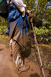 One of the ways to access the Alakai Swamp, part of the Alakai Wilderness Preserve on the island of Kauai in Hawaii is via the typically very muddy and slippery Pihea Trail. Pictured is a hiker at the end of the day after having hiked both trails. Nearly all the mud actually came from the Pihea Trail and not the Alakai Swamp Trail. The Alakai Swamp Trail is built over raised boardwalks for most of the trail to protect the swamp.