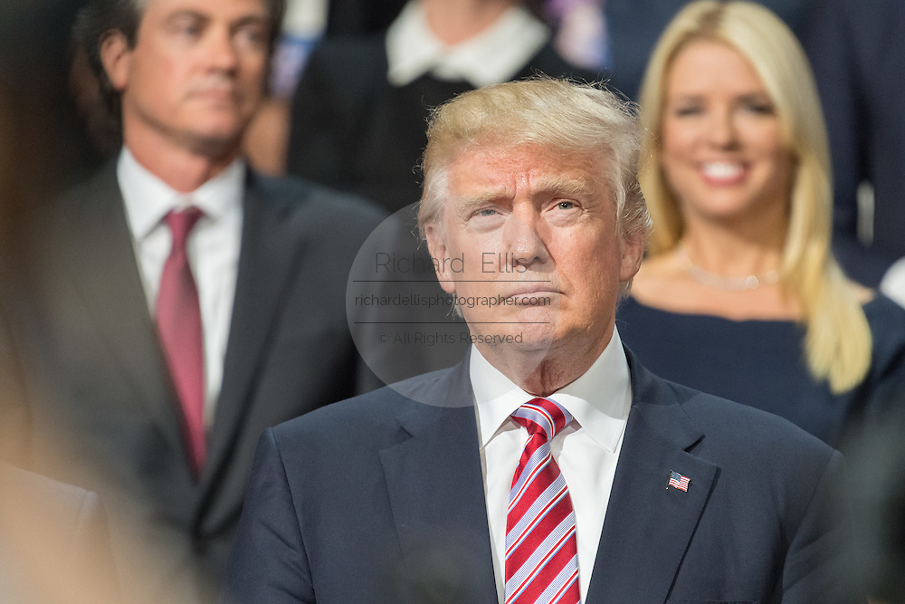 GOP Presidential nominee Donald Trump listens to Senator Ted Cruz speak from the VIP box during the third day of the Republican National Convention July 20, 2016 in Cleveland, Ohio.