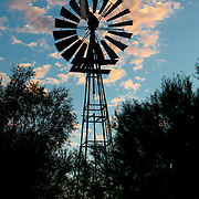 Windmill at sunrise used to pump the underground water in the dry Namibian plains.