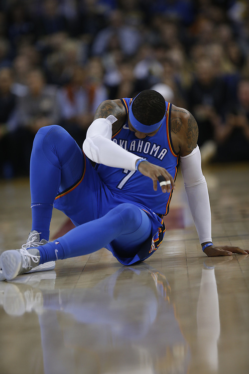 Oklahoma City Thunder forward Carmelo Anthony (7) injures his ankle during the first half of an NBA game between the Golden State Warriors and Thunder at Oracle Arena, Tuesday, Feb. 6, 2018, in Oakland, Calif. Anthony later left the game with a sprained right ankle.