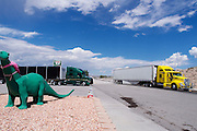 Twee grote vrachtwagens rijden weg bij een tankstion in Alamo, Nevada.<br />