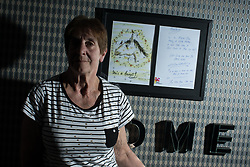 © Licensed to London News Pictures . 06/07/2017 . Manchester , UK . BARBARA DRANSFIELD poses alongside a framed copy of a hand-drawn card from Charles Salvador to her , on the wall of her living room . Artwork by convicted criminal  Charles Salvador (previously Charles Bronson) has been sold on behalf of Salvador to raise a £1,000 to support Barbara and Len Dransfield . Barbara , who has become friendly with Salvador , was brought the money and a card by Salvador's fiance , Paula Wiliamson . Barbara Dransfield was brutally assaulted by masked robbers as she sat at home in her wheelchair . She suffered extensive injuries to her face and body . Photo credit : Joel Goodman/LNP