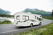 USA, Alaska, recreational vehicle driving on road, side view