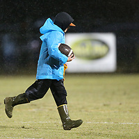 Ty Long, 13, runs the ball back to the sidelines to dry it before the next play during Friday night's game at Ripley.