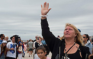 20110911 - Long Beach , NY - Debbie Portwood raises her hand in prayer during a paddle out in remembrance of 9/11 as part of a beach mass and ecumenical service at National Boulevard Beach.  . .Photo by Isabel Slepoy / LI Herald