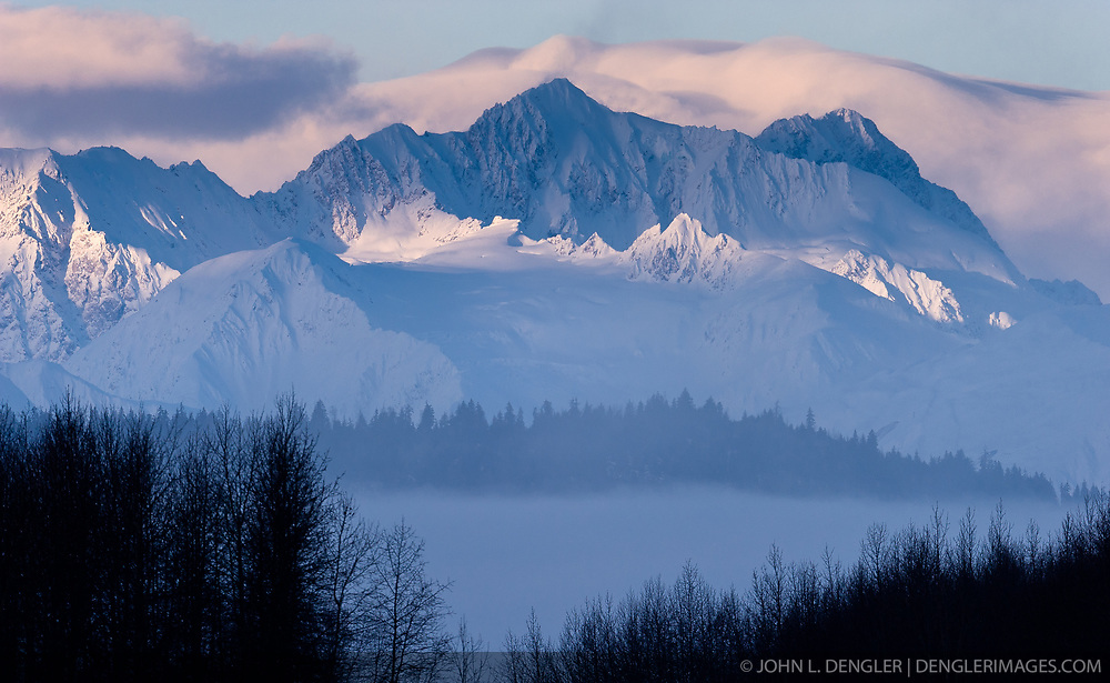 The Takhinsha Mountains near Haines, Alaska are bathed in the morning sunlight in this photo taken from the Alaska Chilkat Bald Eagle Preserve along the Chilkat River. Mountains in the Haines area are a popular destination for heli-skiing.