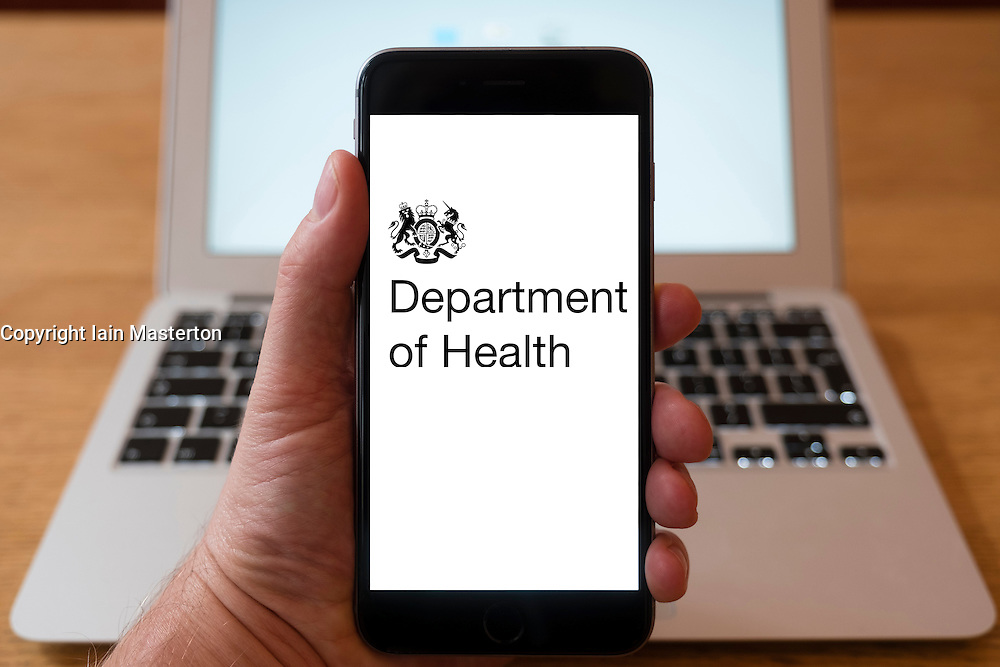 Using iPhone smartphone to display logo of the Department of Health, UK Government,
