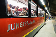 Passengers wait iinside the east face of the Eiger at Eismeer Station (3159 m) of Jungfraujoch Railway in Bern canton, Switzerland, the Alps, Europe. Engineering the dramatic cog-wheel Jungfraujochbahn required 16 years (1898-1912) to carve through the Eiger and Mönch for 7 kilometers (4.3 mi), with gradients of up to 25%. Kleine Scheidegg entry station can be reached by trains from Grindelwald and Lauterbrunnen. The train ride from Kleine Scheidegg to Jungfraujoch (the highest railway station in Europe) takes 50 minutes including stops at Eigerwand and Eismeer viewing portals. Downhill return takes just 35 minutes. The Swiss Alps Jungfrau-Aletsch region is honored as a UNESCO World Heritage Site.