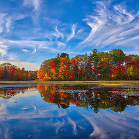 New England fall foliage brilliance at the Factory Pond in Holliston, MA. This autumn photo was inspired by the red glorious fall colors and amazing pond reflection. The photograph was taken at the site where the Darling Woolen Mill stood. The mill was lost to a fire in 1933. <br />