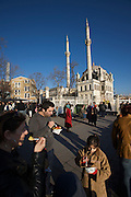 Istanbul. Ortako?y. People having a typical snack near Ortako?y Mosque and Bosporus Bridge: barbecued potato.