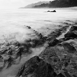 Coastal rock forms and moving water on a Costa Rican beach.
