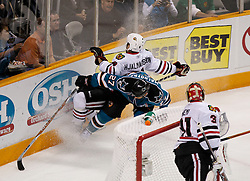 May 18, 2010; San Jose, CA, USA; San Jose Sharks center Manny Malhotra (27) checks Chicago Blackhawks defenseman Niklas Hjalmarsson (4) into the boards during the first period of game two of the western conference finals of the 2010 Stanley Cup Playoffs at HP Pavilion.  The Blackhawks defeated the Sharks 4-2. Mandatory Credit: Jason O. Watson / US PRESSWIRE