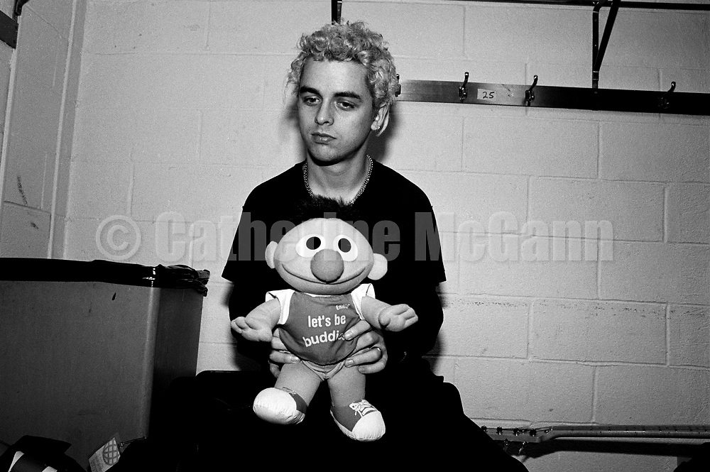 """NEW YORK - 1994:  Billie Joe Armstrong of Green Day poses for a portrait holding a stuffed doll of Ernie from """"Sesame Street""""  printed with the words """"Let's Be Buddies"""" backstage at Madison Square Garden in 1994 in New York City, New York. (Photo by Catherine McGann)..Copyright 2010 Catherine McGann"""