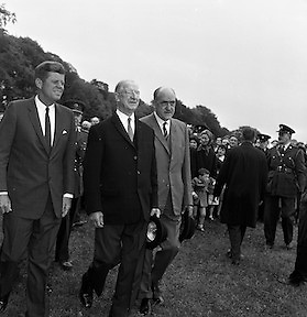 President John F. Kennedy exits the U.S. Embassy to board a helicopter to take him to London to meet Mr. Harold MacMillan. He is accompanied by President Eamon de Valera and Frank Aiken, TD, Minister for External Affairs..29.06.1963