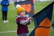 A young Scunthorpe United fan waves a British Steel flag before the players walk onto the pitch during the EFL Sky Bet League 1 match between Scunthorpe United and Rotherham United at Glanford Park, Scunthorpe, England on 10 February 2018. Picture by Craig Zadoroznyj.