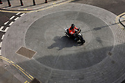 Aerial view of scooter bike rider as he crosses circles of a City of London roundabout.