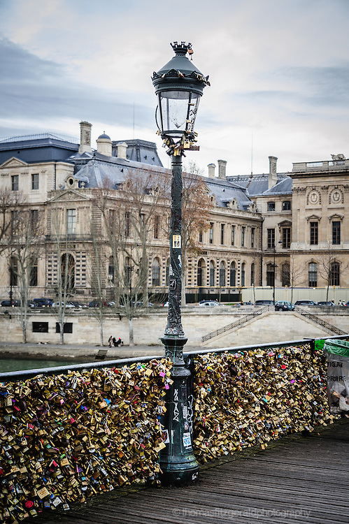Street light on Pont Des Arts, Paris, with the bridge covered in Love Locks