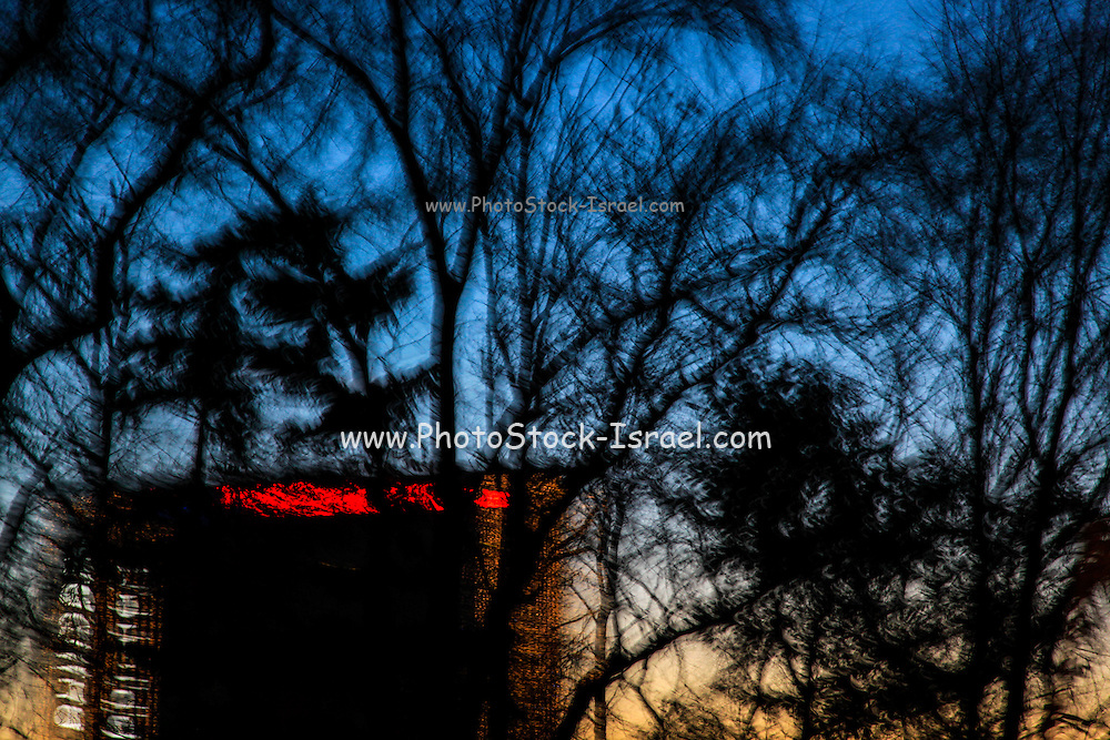 Motion blured trees and landscape abstract at sunset with red lights