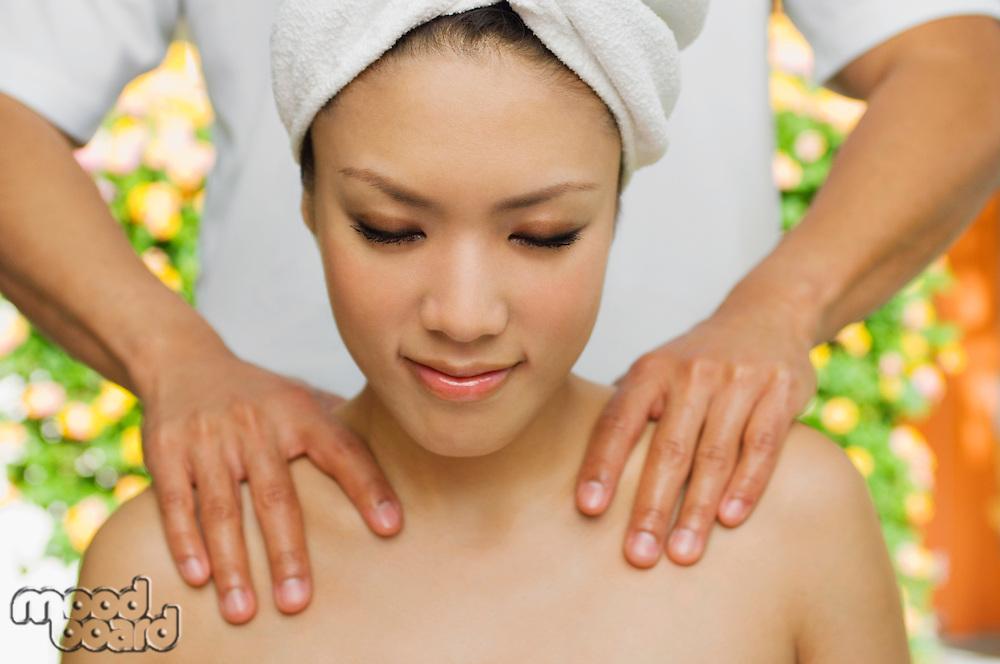Young woman having shoulder massage at health spa