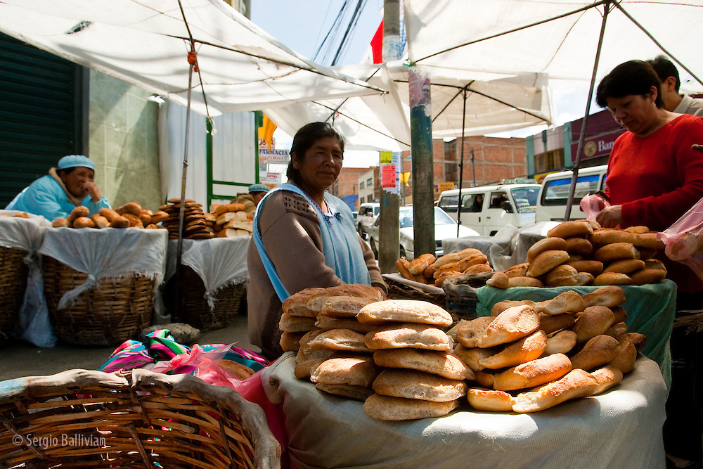 Bread merchants sit surrounded by fresh-baked bread early in the morning in La Paz, Bolivia.  The open-air markets are typical of Bolivia and where the best produce is found, especially on market days.