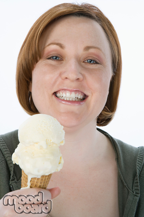 Mid-adult woman holding ice cream cone, portrait