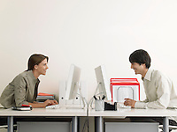 Business Man and Woman Working on Computers Face to Face